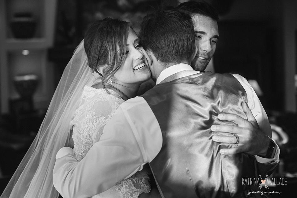bride and groom hug family