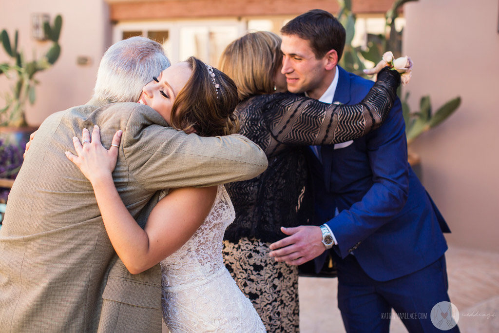 Bride and groom hug family members