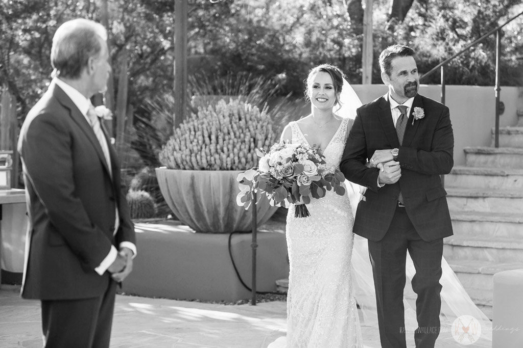 The bride walks arm in arm with her Dad as she begins her stroll down the aisle to be wedded.